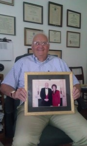U.S. Coast Guard Capt. (ret.) Richard Fremont-Smith, a life-long Red Cross volunteer, poses in his home office holding a picture of him with former Red Cross President Elizabeth Dole.