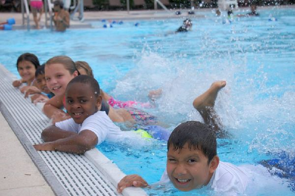 Children learn to swim in a Red Cross swim class.