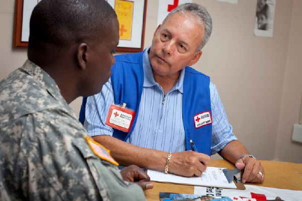 Red Cross Service to the Armed Forces volunteer with a service member.